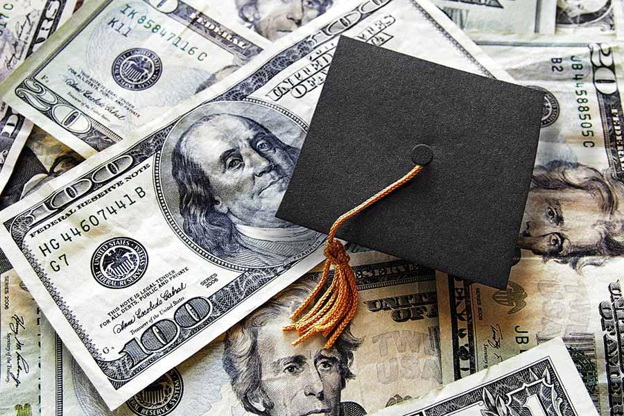 graduation cap on dollar bills